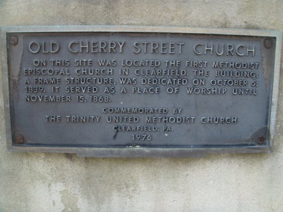 "Marker near CNB Bank on Cherry Street marking the Old Cherry Street Church.  It reads ""On this site was located the first Methodist Episcopal Church in Clearfield. The building, a frame structure, was dedicated on October 5, 1839. It served as a place of worship until November 15, 1868. Commemorated by The Trinity United Methodist Church Clearfield, PA. 1976"""